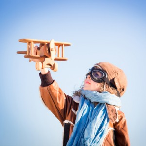 A Little Girl Flying A Wooden Aeroplane With A Pilot Outfit On