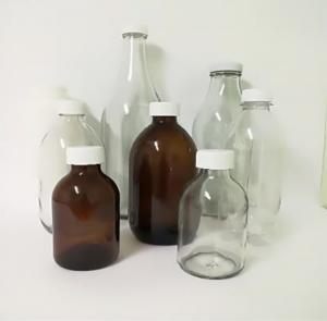 Glass Bottles Of Varying Sizes With White Bottle Caps